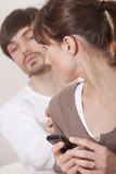 Secrets in relationship. Woman hiding her mobile phone from curious man Stock Images