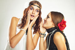 Secrets and rumors. Two old-fasioned girlfriends talking over grey background stock photo