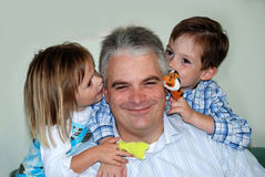Secrets. Siblings  whispering secrets in fathers ears Royalty Free Stock Images