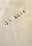 Secrets on textured paper - diagonal. 'Secrets' printed on textured paper Royalty Free Stock Image
