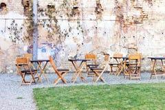 Secteur extérieur de café de cour avec les tables et la chaise en bois, la pelouse d'herbe verte et le mur de briques shbby ruiné Images libres de droits