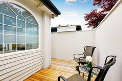 Secteur fermé de patio avec deux chaises et plancher en bois Image stock
