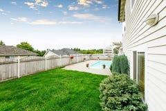Secteur spacieux d'arrière-cour avec la barrière en bois et la pelouse soignée Photo libre de droits