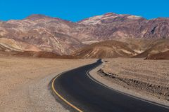 A highway curving through a barren desert landscape towards a range of colorful rugged mountains. A section of Artist`s Drive in Death Valley National Park royalty free stock photography