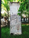 Section of Berlin Wall surrounded by green royalty free stock photography