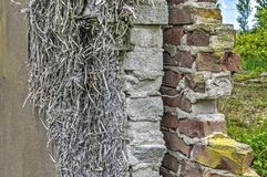Section of a brick wall. Section through a wall of a partly demolished buidling with two different kinds of brickwork, a cavity, insulation material and plaster Royalty Free Stock Photography