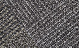 Gray carpet with diagonal lines. A section of carpet showing adjoining corners with intersecting diagonal lines stock photography