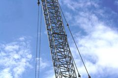 Section of crane against a blue sky abstract. The middle section of a steel crane against a blue sky with white cloud Stock Image