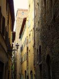 Section of a crooked narrow street in Florence leading between old houses. Section of a crooked narrow street in Florence, Italy, between old houses royalty free stock image