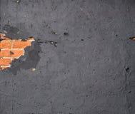 Section of damaged wall. Revealing brickwork underneath. Orange brickwork and black painted plaster royalty free stock photography