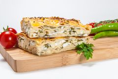 Section de lasagne avec du fromage sur le conseil en bois photos libres de droits