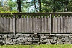 Section de mur en pierre empilé avec la barrière en bois affligée Image stock