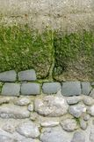 Section of a decorative weathered old wall by the sea in Normandy, stone in part concrete, with algae and moss, copy space, space. Section of a decorative stock images