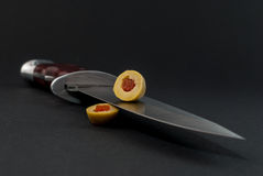 Section of green olive filled with red pepper on knife blade on black background Royalty Free Stock Images