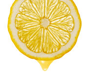Section lemon with drop. The detailed photo on a gleam. It is isolated on a white background Stock Photos