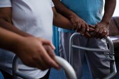 Section médiane d'ami aidant la femme dans la marche avec le marcheur Images stock