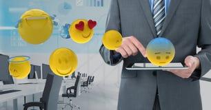 Section médiane d'homme d'affaires utilisant le comprimé numérique avec de divers emojis Photos libres de droits