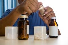 Section médiane d'homme supérieur prenant des médecines dans la maison de repos Photos libres de droits