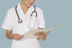Section médiane d'un rapport médical de lecture de docteur féminin au-dessus de fond bleu-clair Photo libre de droits
