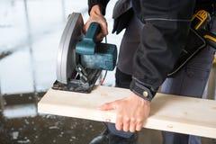 Section médiane de charpentier Using Electric Saw pour couper le bois Photographie stock