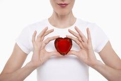 Section médiane de femme tenant le coeur en verre rouge Photos stock