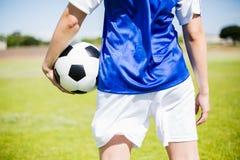 Section médiane de footballeur se tenant avec une boule image libre de droits