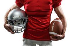 Section médiane de joueur de football américain dans le débardeur rouge tenant le casque et la boule photo libre de droits
