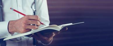 Section médiane de l'écriture d'homme d'affaires dans son carnet Photographie stock