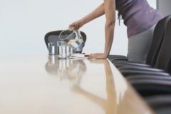 Section médiane de l'eau de versement de main-d'œuvre féminine dans des verres dessus confer Photo stock