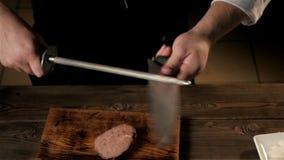 Section médiane de la cuisine masculine de message publicitaire de Sharpening Knife In de chef banque de vidéos