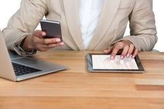 Section médiane de la femme d'affaires à l'aide du téléphone portable et du comprimé numérique avec l'ordinateur portable sur la  Image libre de droits
