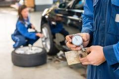 Section médiane de mécanicien Holding Analog Gauge dans le garage Images stock