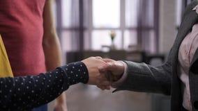 Section médiane de poignée de main du ` s de couples avec l'agent immobilier banque de vidéos