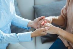 Section médiane de thérapeute tenant les mains patientes photographie stock libre de droits