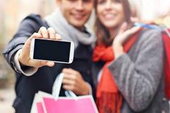 Section médiane des achats de couples dans la ville avec le smartphone Photographie stock