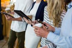 Section médiane des amis à l'aide du comprimé numérique et du téléphone portable Image stock