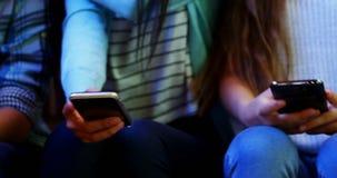Section médiane des amis d'école à l'aide du téléphone portable dans le couloir banque de vidéos