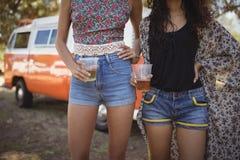 Section médiane des amis féminins tenant des verres de bière Images stock