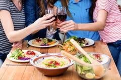 Section médiane des amis grillant des verres de vin rouge Photographie stock libre de droits