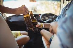 Section médiane des amis grillant la bière Images stock