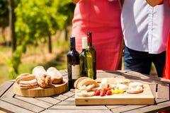 Section médiane des amis par des bouteilles de nourriture et de vin sur la table Photos libres de droits