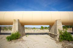 Section of Metal Pipeline. Massive metal piping crosses the Mojave desert on large cement girders Royalty Free Stock Image