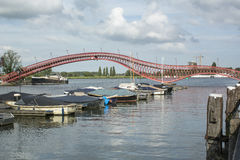 Section of modern red pedestrian bridge with several boats Stock Image