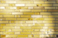 Section of an old partially weathered and polluted building wall of yellow to brownish clinker bricks with soft shadows of trees stock photography
