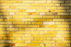 Section of an old partially weathered and polluted building wall of yellow to brownish clinker bricks with soft shadows of trees royalty free stock image