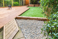 A section of a residntial garden, yard with wooden decking,. Patio over a fish pond, a section of artificial grass and an area of stone pebble. There is a Stock Image