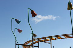 Section of Rollercoaster track with lights. A section of rollercoaster track with overhead lights and a blue sky with whispy cloud Royalty Free Stock Photography