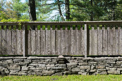 Section of Stacked Stone Wall with Distressed Wood Fence. Stock Image