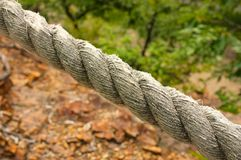 Section of thick rope dividing land and trees.  Royalty Free Stock Photos