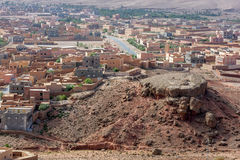 A section of the village of Tinerhir in Morocco with an unusual rock formation in the foreground. Stock Photos
